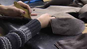 Worker making seal skin mitts - CBC